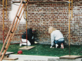Photo of two participants scrapping bottom of bare brick wall (with scaffolding in foreground).