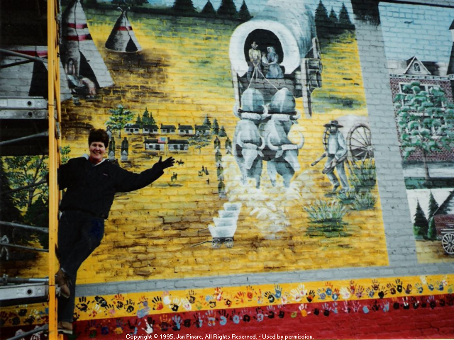 Photo of a participant waving from the scaffolding (near ground level and far left side); the background of the mural shows a close-up of an ox driven covered wagon.