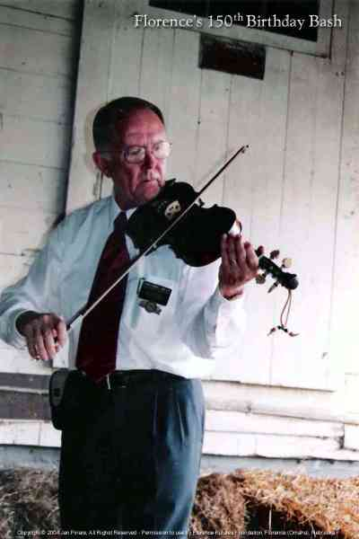 Elder Thurber plays fiddle at the Florence Mill.